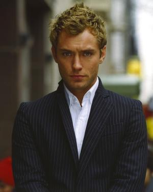Jude Law Looking at the Camera wearing a Suit and White Undershirt in a Portrait by Movie Star News