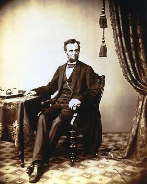 Lincoln Abraham in Formal Suit on Chair by Movie Star News