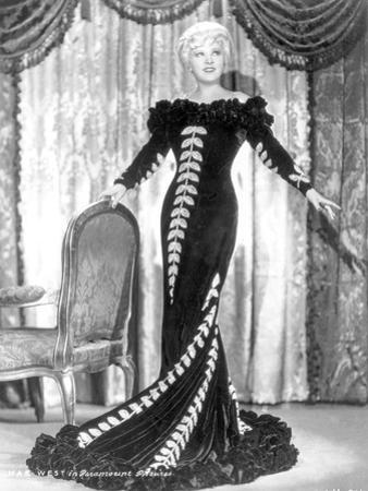 Mae West standing in Black Long Gown with Arm's Open by Movie Star News