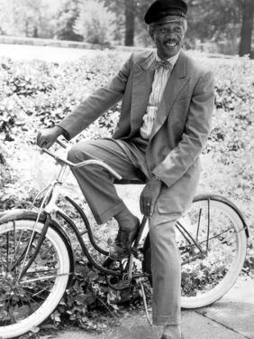 Morgan Freeman Riding Bike in Suit With Cap by Movie Star News