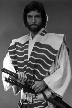 Richard Chamberlain standing in Swordsman Attire With Sword by Movie Star News