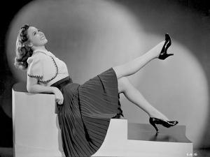 Susan Hayward sitting and Leaning in Skirt with High Heels by Movie Star News