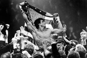 Sylvester Stallone Carried by a Men and Holding a Flag by Movie Star News