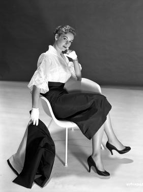 Vera Miles casually posed sitting in a white chair, wearing white chiffon top by Movie Star News