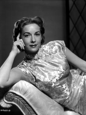 Vera Miles laying on a chaise lounger wearing oriental dress, with head propped into her hand by Movie Star News