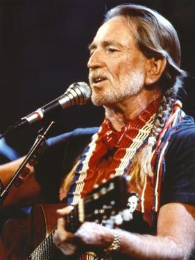 Willie Nelson Playing Guitar in Black Shirt by Movie Star News