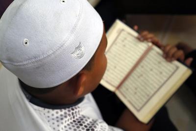 https://imgc.allpostersimages.com/img/posters/muslim-boy-learning-quran-at-islamic-school-with-kufi-hat_u-L-Q1GYKWM0.jpg?artPerspective=n