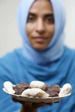 https://imgc.allpostersimages.com/img/posters/muslim-woman-offering-ramadan-pastries_u-L-Q1GYMGP0.jpg?artPerspective=n