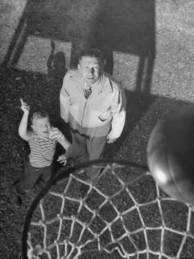 Oklahoma A&M Basketball Coach Hank Iba Watching a Young Boy Shooting a Basket by Myron Davis