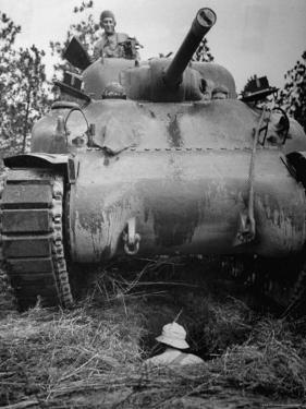 Oncoming View of Tank About to Pass over Foxhole in Which a Soldier is Crouched Down by Myron Davis