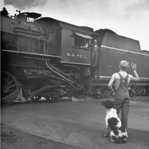 Young Boy and His Dog Standing at the Crossing as a Train Rides Through by Myron Davis