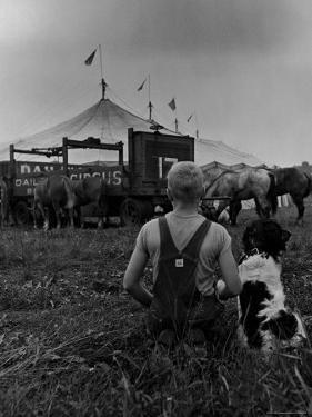 Young Boy and His Dog Watching the Circus Tents Being Set Up by Myron Davis