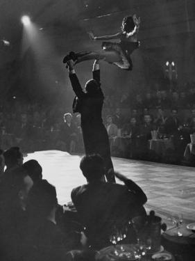 Can Can Dancer Held Up in the Air by a Performing Gentleman at the Paris Show by Nat Farbman