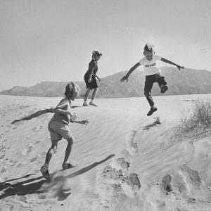 Children Playing in the Desert Sand by Nat Farbman
