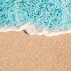 Soft Wave of Blue Ocean in Summer. Empty Sandy Beach Background with Copy Space for Text. by Natalia Zakharova