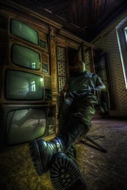 Male Figure in Abandoned Building with Televisions by Nathan Wright