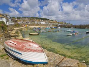 Small Unturned Boat on Quay and Small Boats in Enclosed Harbour at Mousehole, Cornwall, England by Neale Clark