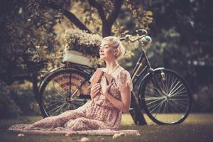 Dreaming Blond Retro Woman with a Book Sitting on a Meadow by NejroN Photo