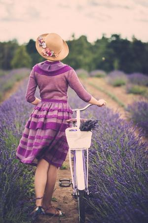 Woman in Purple Dress and Hat with Retro Bicycle in Lavender Field