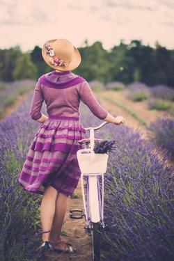 Woman in Purple Dress and Hat with Retro Bicycle in Lavender Field by NejroN Photo