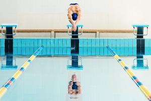 Young Muscular Swimmer Jumping from Starting Block in a Swimming Pool by NejroN Photo