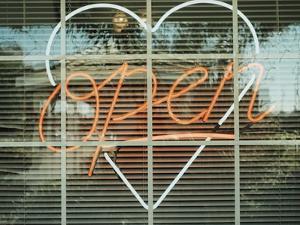 Neon 'Open' sign framed in a heart-shape in a window