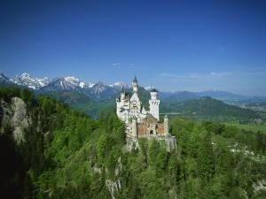 Neuschwanstein Castle on a Wooded Hill with Mountains in the Background, in Bavaria, Germany
