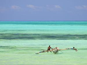 Tanzania, Zanzibar, Unguja, Jambiani, a Man Sits on His Boat Near the Shore by Nick Ledger