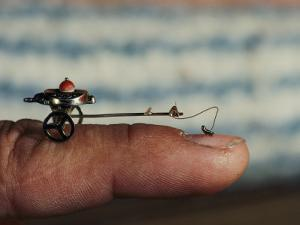 A Flea Pulls a Small Cart Along an Outstretched Finger by Nicole Duplaix