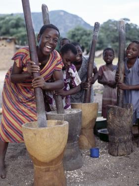 Cheerful Young Girls Pound Corn Outside Families' Homes Near Monkey Bay, South End of Lake Malawi by Nigel Pavitt