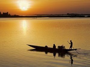 Mopti, at Sunset, a Boatman in a Pirogue Ferries Passengers across the Niger River to Mopti, Mali by Nigel Pavitt