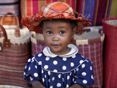 Young Girl Beside a Road-Side Stall Near Antananarivo, Capital of Madagascar by Nigel Pavitt