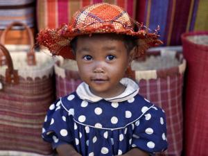 Young Girl Beside a Road-Side Stall Near Antananarivo, Capital of Madagascar by Nigel Pavitt
