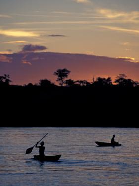 Boaters on Amazon River at Sunset, Amazon River Basin, Peru by Nik Wheeler