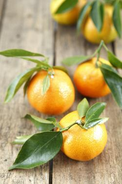 Clementines with Leaves on Wood by Nikky