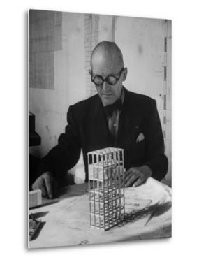 Architect Le Corbusier Studying Architectural Plans and Small Model of Building in His Office by Nina Leen