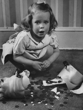 Little Girl Leaning over Her Broken Piggy Bank by Nina Leen
