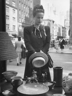 Maeve Brennan of Harper's Bazaar Looking Through Store Window by Nina Leen