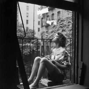 Model Jean Patchett on Fire Escape of Ford Modeling Agency, New York, New York, 1941 by Nina Leen