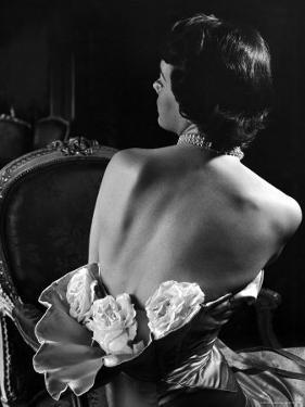 Model Wearing Mother of Pearl Satin Gown with roses tucked in waist by Balmain by Nina Leen