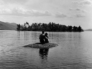 Private Island, Young Couple Embracing on a Small Rock Protruding from the Waters of Lake George by Nina Leen