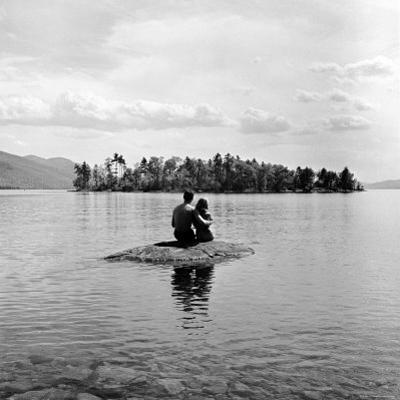 Young Couple Embracing on Small Rock Protruding from the Waters of Lake George