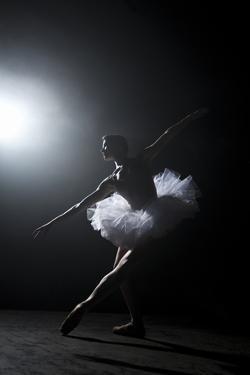 Ballerina Performing on Stage under Spotlight by Nisian Hughes