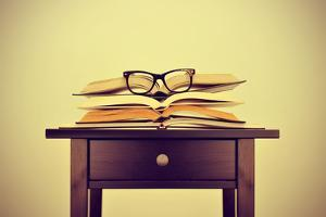 A Pile of Books and a Pair of Eyeglasses on a Desk, Symbolizing the Concept of Reading Habit or Stu by nito