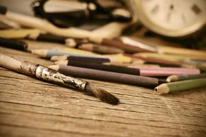 A Stained Brush, Colored Pencils of Different Colors, a Pair of Eyeglasses and an Old Clock on a Ta by nito
