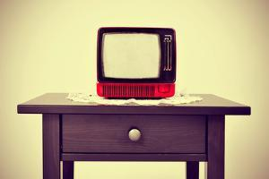 An Ancient Red Television on a Table with a Retro Effect by nito
