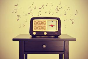 An Antique Radio Receptor on a Desk and Musical Notes, with a Retro Effect by nito