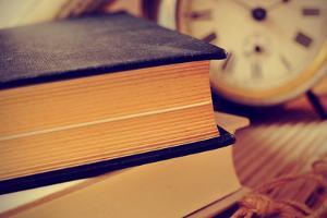Closeup of a Pile of Old Books and an Old Alarm Clock on a Desk, with a Retro Effect by nito
