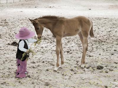 Child in Western Wear Feeding a Pony