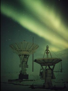 Antennas Point Skyward under the Glowing Aurora Borealis by Norbert Rosing